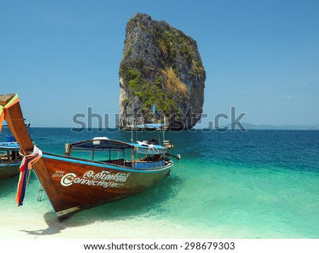 KRABI, THAILAND - FEBRUARY 15, 2015: Traditional Thai wooden longtail boat waits on the shore of Bamboo Island for passengers on a day trip from Phi Phi Island.