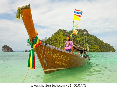 Krabi, Thailand - July 26, 2014: Long tail wooden boats (traditional way of transport) and boat operator with island background and blue sky in Tup island, one of Krabi's nearest island.