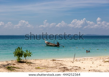 Krabi, Thailand - June 12th 2016 - Traditional thai boat in an amazing tropical beach in Krabi area in Thailand, Asia.