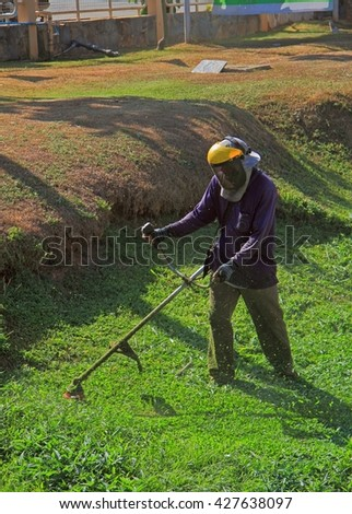 KRABI, THAILAND - MARCH 29, 2015: man is trimming grass outdoor in Krabi province of Thailand