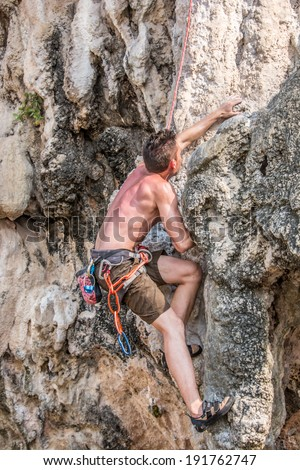 Krabi,Thailand - March 29, 2014: Rock climber climbing on Railay beach in Krabi, Thailand. Railay beach is one of the most popular rock climbing locations in Asia.