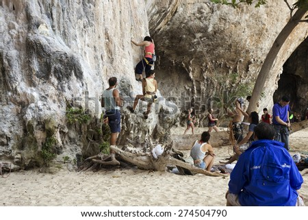 KRABI, THAILAND - MARCH 28, 2015: Rock climbers climbing the wall on Phra Nang beach, One of the most popular rock climbing locations in Krabi, Thailand