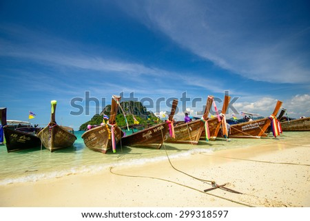 KRABI, THAILAND - Nov 11, 2014: Traditional Thai wooden longtail boat waits on the shore of Bamboo Island for passengers on a day trip from Phuket Island.