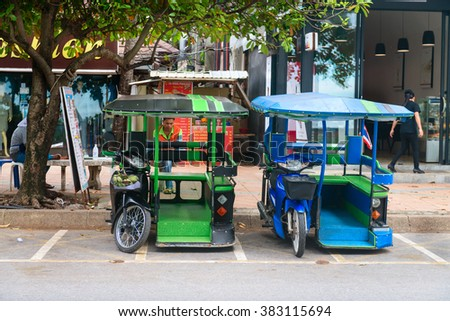 KRABI, THAILAND - 13 OCT 2014: Green and blue tuk tuk used as tourist taxis parked under a tree in the public street at Ao Nang Krabi, Thailand