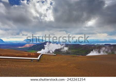Krafla Lake neighborhood. Summer Iceland. Steam rises above the hot ground. Pipeline to transport hot water - stock photo
