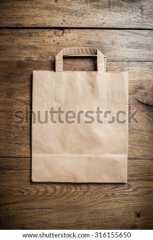 Kraft paper bag with handles on vintage wood background - stock photo