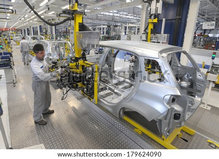 KRAGUJEVAC, SERBIA - CIRCA APRIL 2012: Workers assembles cars at Fiat Cars Serbia factory, circa April 2012 in Kragujevac. - stock photo