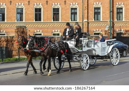 KRAKOW - APRIL 08,2014: Tourists enjoy a ride in horse-drawn carriage.