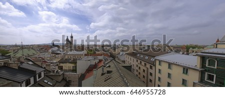 Krakow panorama above house roofs with cloudy sky, Poland