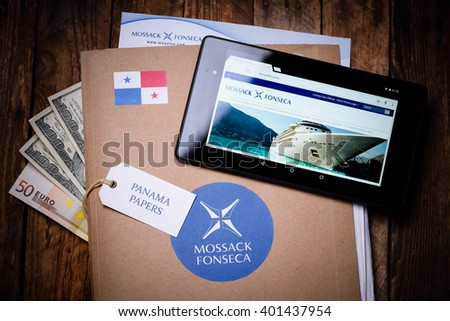 KRAKOW, POLAND - APRIL 5, 2016 : Folder with Mossack Fonseca logo, US and EU currency and tablet with Mossack Fonseca web site.  - stock photo