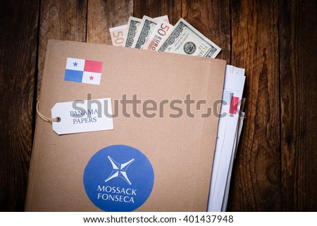 KRAKOW, POLAND - APRIL 5, 2016 : Folder with Mossack Fonseca logo with US and EU currency. Panama Papers are millions leaked documents with information about offshore companies.