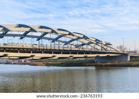 KRAKOW, POLAND - DEC 10, 2014: steel bridge over Vistula river in Krakow. Public transport connects two sides of Krakow city separated by Vistula river.