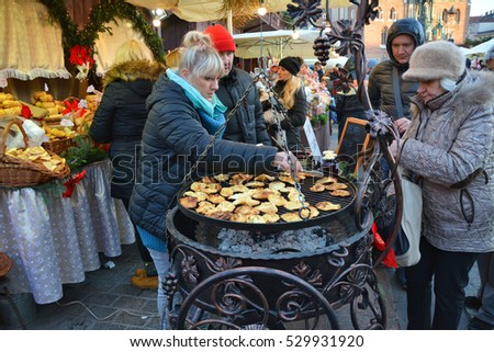 KRAKOW, POLAND - DECEMBER 4, 2016:  Christmas market stall with Grilled cheese oscypek. The annual Christmas market in the Market Square is a popular tourist attraction