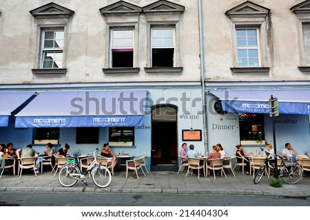KRAKOW, POLAND - JUL 31: Young people sitting outdoor around the tables of restaurant in old city on July 31 2014. Krakow with popul. of 800,000 people has 2.35 mill. foreign tourists annually  - stock photo