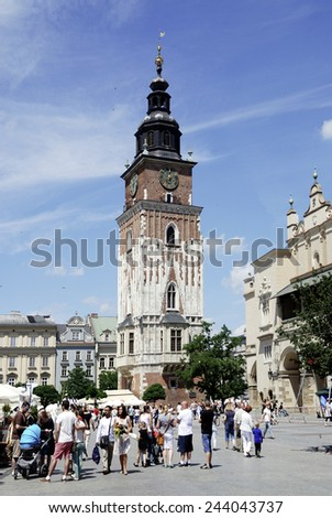 Krakow, Poland - July 13, 2014: Tourists in front of the Town Hall Tower on the Market Square in Krakow in Poland.