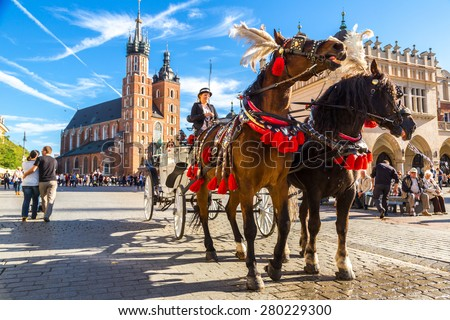 KRAKOW, POLAND - JUNE 16: Horse carriages at main square in Krakow in a summer day, Poland on June 16, 2014 - stock photo