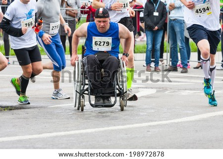 KRAKOW, POLAND - MAY 18 : Cracovia Marathon. Unidentified handicapped man in  marathon on a wheelchair on the city streets on May 18, 2014 in Krakow, POLAND  - stock photo