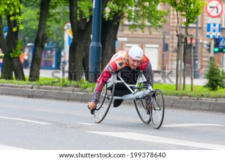 KRAKOW, POLAND - MAY 28 : Cracovia Marathon. Unidentified handicapped man in  marathon on a wheelchair on the city streets on May 18, 2014 in Krakow, POLAND  - stock photo