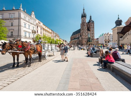 Krakow, Poland - May 16, 2013. Tourists visiting main market square in front of St. Mary's Basilica, in Krakow, Poland, Europe. Old medieval  town of Cracow listed as unesco heritage site.