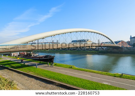 KRAKOW, POLAND - NOV 2, 2014: Bernatka bridge over Vistula river on sunny autumn day in city of Krakow, Poland. This metal construction is 145 meters long and is a famous landmark of the city.