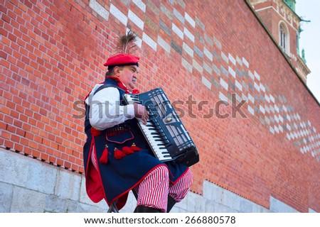 KRAKOW, POLAND - NOV 11, 2014: Street musician wore in traditional Poland dress playing on the street of Krakow.  - stock photo