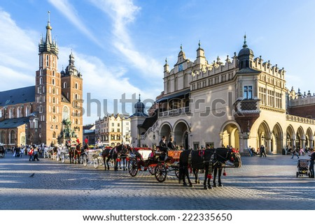 KRAKOW, POLAND - OCT 7, 2014: Horse carriages in front of Mariacki church on main square of Krakow city. Taking a horse ride in a carriage is very popular among tourists visiting Krakow - stock photo