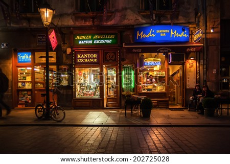 KRAKOW, POLAND - OCTOBER 3, 2009: Night bars and shops on the streets of Krakow near Main Market Square. At roughly 40.000 square meters it is the largest medieval town square in Europe.