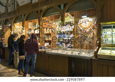 KRAKOW, POLAND - OCTOBER 26, 2014: Tourists shop in Sukiennice Cloth Hall. Krakow's Old Town is a UNESCO World Heritage Site with Sukiennice being its top shopping place