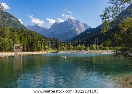 KRANJSCA GORA, SLOVENIA - JULY 31, 2017 - Lake Jasna: reflections on the water, holidays makers on the lakeshore, mountains on background