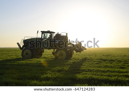 Krasnodar, Russia - April 27, 2017: Tractor with high wheels is making fertilizer on young wheat. The use of finely dispersed spray chemicals. Tractor on the sunset background.