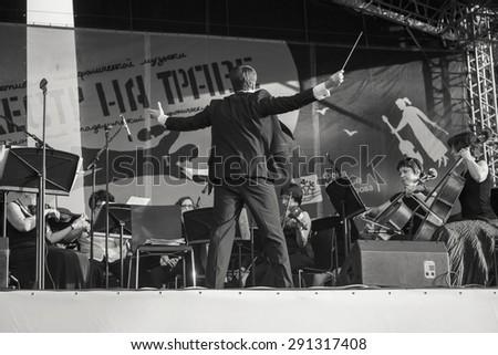 "Krasnoyarsk, Russia - June 18, 2015: Summer Youth Festival of symphonic music ""Band on the grass"" on the island Tatyshev - conductor Nikolai Balyshev - stock photo"