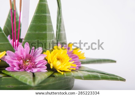 Krathong, the hand crafted floating candle made of floating part decorated with green leaves colorful flowers and many sorts of creative materials . - stock photo