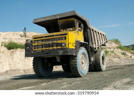 Kremenchug, Ukraine - 27 June 2008. Yellow dump truck driving on a road in a stone quarry - stock photo