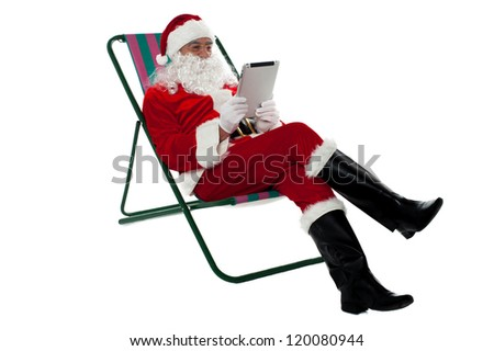 Kris Kringle relaxing on chair and using electronic tablet. Isolated on white. - stock photo