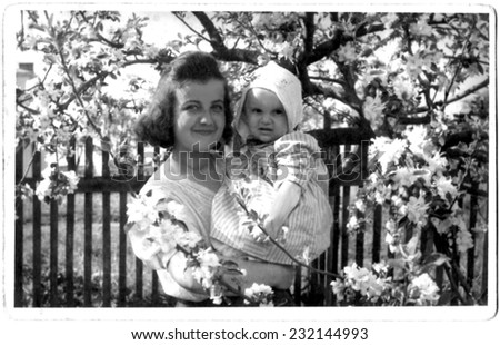 KROSNO,POLAND - CIRCA 1946 : vintage photo of happy young woman with her small daughter in blossoming orchard