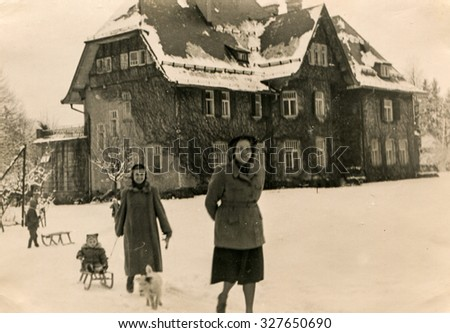 KRYNICA, POLAND, CIRCA 1952: Vintage photo of two women with children in winter - stock photo