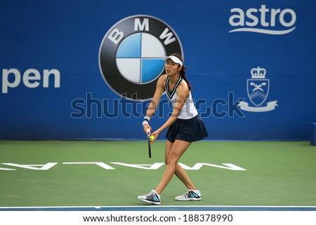 KUALA LUMPUR - APRIL 20, 2014: Chan Hao-Ching of Taiwan serves at the doubles final of the BMW Malaysian Open Tennis in Kuala Lumpur, Malaysia. She partners Timea Babos of Hungary to emerge winners. - stock photo