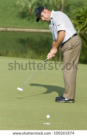 KUALA LUMPUR - APRIL 15: Hennie Otto of South Africa makes a putt on to 16th green during 3rd round of Maybank Malaysian Open 2012 at Kuala Lumpur Golf & Country Club on April 15, 2012