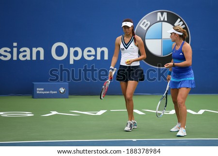 KUALA LUMPUR - APRIL 20, 2014: Timea Babos of Hungary (blue) discusses Chan Hao-Ching of Taiwan at the doubles final of the BMW Malaysian Open Tennis in Kuala Lumpur, Malaysia. They emerge winners. - stock photo