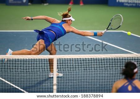 KUALA LUMPUR - APRIL 20, 2014: Timea Babos of Hungary (blue) returns during the doubles final of the BMW Malaysian Open Tennis in Kuala Lumpur, Malaysia. She partners Chan Hao-Ching to emerge winners. - stock photo