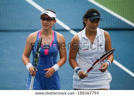 KUALA LUMPUR - APRIL 19, 2014: Zheng Saisai and Chan Yung-Jan (white dress) discuss tactics between serves in their women's semifinals of the BMW Malaysian Open tennis is Kuala Lumpur, Malaysia. - stock photo