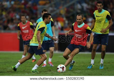 KUALA LUMPUR - AUGUST 09: FC Barcelona 's Xavi Hernandez (yellow) takes on Andres Iniesta (red) during training at the Bukit Jalil Stadium on August 09, 2013 in Malaysia.