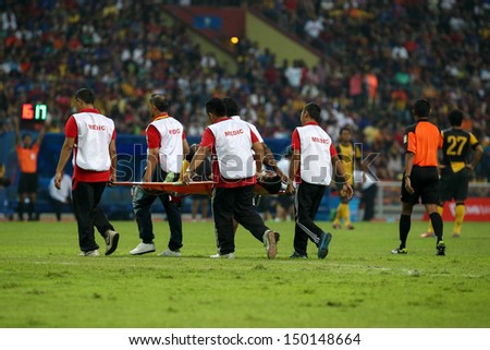 KUALA LUMPUR - AUGUST 10: Medics carry out an injured player on a stretcher in a Malaysia vs Barcelona friendly match at the Shah Alam Stadium on August 10, 2013 in Malaysia. Barcelona wins 3-1. - stock photo