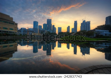 Kuala Lumpur city at a lake with beautiful sky reflection during sunrise (soft focus, shallow DOF, slight motion blur)