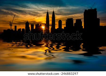 Kuala Lumpur City Center in silhouette during sunrise surrounding with water flood. digital compositing with colour tone, water reflection and ripple effects.