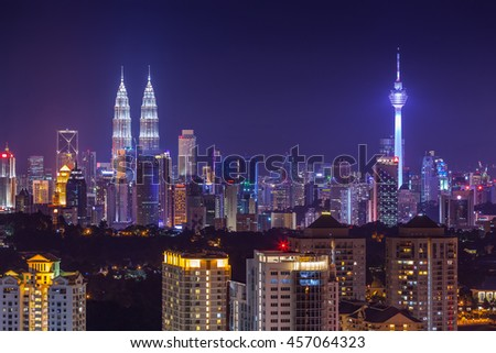 Kuala Lumpur city skyline vibrantly lit at dusk, viewed from east