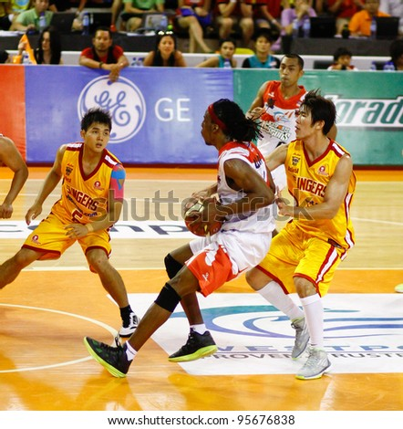 KUALA LUMPUR - FEBRUARY 19: Malaysian Dragons' Tiras Wade (white) dribbles in against the Singapore Slingers at the ASEAN Basketball League match on Feb 19, 2012 in Kuala Lumpur, Malaysia.  Dragons won 86-71. - stock photo