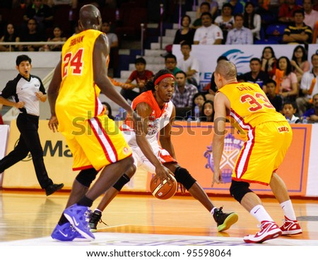 KUALA LUMPUR - FEBRUARY 19: Malaysian Dragons' Tiras Wade (white) dribbles in at the ASEAN Basketball League match against Singapore Slingers on Feb 19, 2012 in Kuala Lumpur, Malaysia. Dragons won 86-71. - stock photo