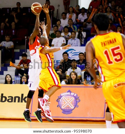 KUALA LUMPUR - FEBRUARY 19:Malaysian Dragons' Tiras Wade (white) makes a jumpshot in at the ASEAN Basketball League match against Singapore Slingers on Feb 19, 2012 in Kuala Lumpur, Malaysia. Dragons won 86-71. - stock photo