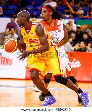 KUALA LUMPUR - FEBRUARY 19: Singapore Slingers' Louis Graham (yellow) dribbles past Tiras Wade at the ASEAN Basketball League match on February 19, 2012 in Kuala Lumpur, Malaysia. Dragons won 86-71. - stock photo